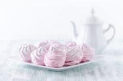 Älskvärda pastellrosmarängar, sefir, marshmallower och en kaffekruka på trätappningtabellen Royaltyfria Foton