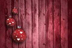 Älskvärda röda kulöra Xmas-kulor på wood bakgrund Fotografering för Bildbyråer