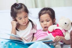 Älskvärda tvilling- barnflickor för syster som två har gyckel som läser en tecknad film Royaltyfri Fotografi