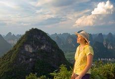 Älskvärda unga kvinnor på solnedgången överst av bergskammarna Royaltyfria Foton