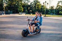 Älskvärda unga lyckliga par som kör den elektriska cykeln royaltyfri fotografi