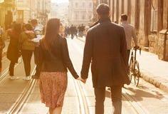 Älskvärda unga par som går ner den soliga gatan royaltyfri foto