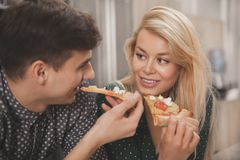 Älskvärda unga par som tillsammans äter pizza på köket arkivfoto