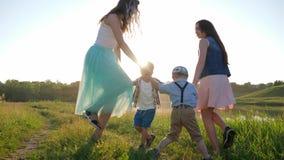 Älskvärda ungar med händer för innehav för rund dans för flickatonåringledning på grön gräsmatta nära den lilla floden arkivfilmer