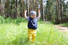 Älskvärt behandla som ett barn att gå i skog mot blommor Fotografering för Bildbyråer