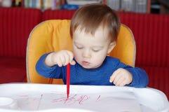 Älskvärt behandla som ett barn målarfärger med den röda pennan Arkivbild