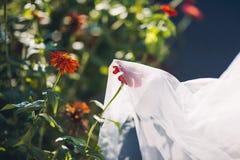 Älskvärt brud- skyler med blommor Royaltyfria Bilder