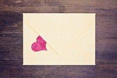 Älskvärt hälsningkort - mailer med röd hjärta Arkivfoto