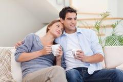 Älskvärt koppla ihop hållande ögonen på dricka tea för TVstunder Royaltyfria Foton
