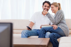 Älskvärt koppla ihop hållande ögonen på TVstunder som äter popcorn Arkivfoto