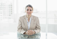 Älskvärt le affärskvinnasammanträde på hennes skrivbord Royaltyfri Fotografi