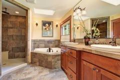 Älskvärt ledar- badrum med stengolvet och den stora duschen arkivbild