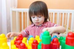 Älskvärt litet barn som spelar hemmastadda plast- kvarter Royaltyfri Foto