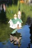 Älskvärt litet hus för and på sjön arkivbild