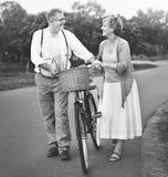 Älskvärt mogna par med en cykel arkivfoton