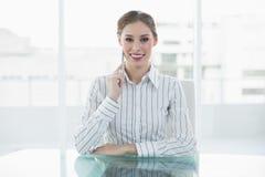Älskvärt tänkande affärskvinnasammanträde på hennes skrivbord som ler på kameran Arkivbilder