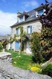 Älskvärt typisk Breton stenhus med blåa slutare och en trädgård med rosor fotografering för bildbyråer