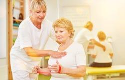Älter mit Theraband an der Physiotherapie lizenzfreie stockfotografie