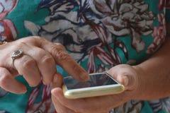 Älter unter Verwendung das mit Berührungseingabe Bildschirm eines Handys, draußen lizenzfreie stockbilder
