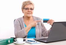 Ältere ältere Frau, die Kreditkarte, zahlend über Internet für Stromrechnungen oder den Einkauf zeigt lizenzfreie stockbilder