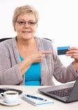 Ältere ältere Frau, die Kreditkarte, zahlend über Internet für Stromrechnungen oder den Einkauf zeigt lizenzfreie stockfotos