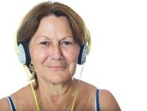 Ältere ältere hispanische Frau, die Musik auf ihren Kopfhörern hört Lizenzfreie Stockfotografie