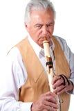 Ältere ältere männliche spielende Ureinwohnerflöte Lizenzfreie Stockfotos