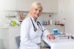 Ältere Ärztin, die an der Kamera lächelt stockbilder
