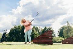 Ältere aktive Frau, die auf einem Golfplatz spielt Stockfoto