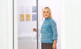 Ältere alte Frau betritt die Bürotür Lizenzfreie Stockfotografie