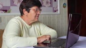 Ältere alte Frau in den Brillen, die zu Hause Internet auf Laptop surfen stock footage