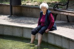 Ältere alte Frau, die Beine im gesunden Heißwasser des Badekurortes sitzt und hält Stockfotografie