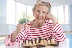 Ältere alte Frau, die Schach, bewegliche Stücke über dem Schachbrett auf großem Glashintergrund spielt Stockbilder