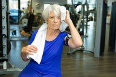 Ältere alte Frau, die weg vom Schweiß weg von der Stirn abwischt Lizenzfreies Stockbild