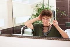 Ältere alte Frau mit einem Spiegel Lizenzfreies Stockbild