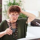 Ältere alte Frau mit einem Spiegel Stockfoto
