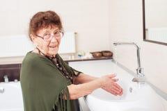 Ältere alte Frau wäscht ihre Hände Lizenzfreie Stockfotos