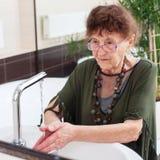 Ältere alte Frau wäscht ihre Hände Lizenzfreies Stockbild