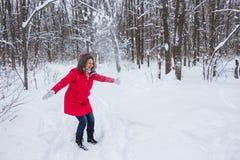 Ältere alte Frau wirft Schnee im Holz im roten Mantel Stockfoto