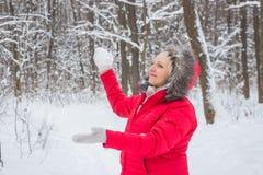Ältere alte Frau wirft Schneeball im Holz im roten Mantel Stockbilder