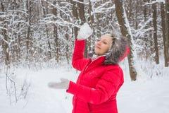 Ältere alte Frau wirft Schneeball im Holz im roten Mantel Lizenzfreies Stockfoto