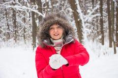 Ältere alte Frau wirft Schneeball im Holz im roten Mantel Stockfotos