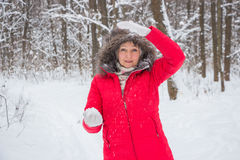 Ältere alte Frau wirft Schneeball im Holz im roten Mantel Stockfoto
