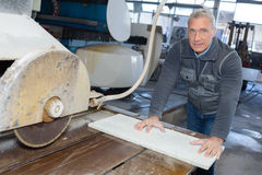 Ältere Arbeitskraft des Porträts, die Sägemaschine verwendet Lizenzfreies Stockbild