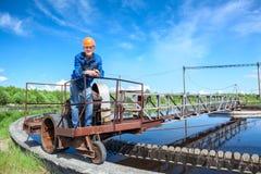 Ältere Arbeitskraft, die auf Einheit der Abwasserbehandlung steht Stockbilder