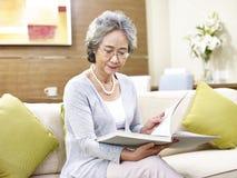 Ältere asiatische Frau, die ein Buch liest Lizenzfreie Stockfotos
