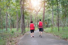 Ältere asiatische Frau mit rüttelndem Betrieb des Mannes oder des persönlichen Trainers im Park stockfotografie
