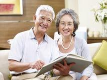 Ältere asiatische Paare, die zusammen ein Buch lesen lizenzfreies stockbild