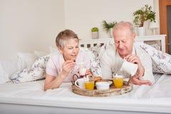 Ältere Bürger, die im Bett frühstücken stockfotos