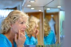 Ältere blonde Frau, die ihre Alternhaut überprüft Lizenzfreies Stockfoto